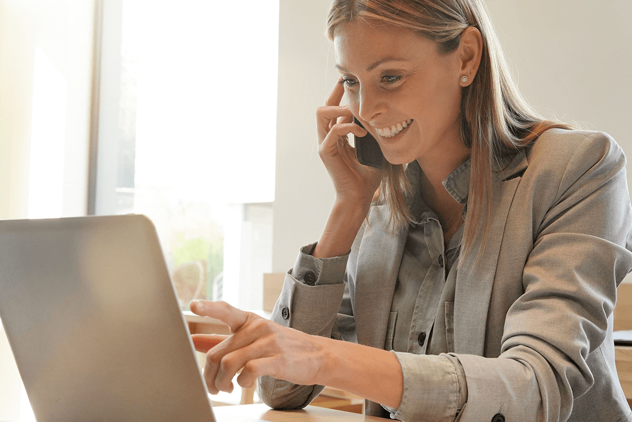 Young female international sales manager at work on the phone and working on laptop